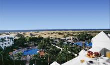 Blick über das Hotelgebäude auf den Pool und den Strand