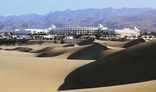 Blick über Sanddünen auf die Hotelanlage