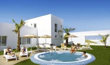 Aussicht auf kleines Hotelgebäude mit Pool und badenden Gästen