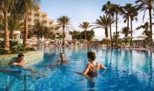 Blick auf Pool mit badenden Gästen und Ausblick auf das Hotelgebäude