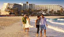 Aussicht vom Strand auf die Hotelanlage mit spazierenden Gästen im Vordergrund