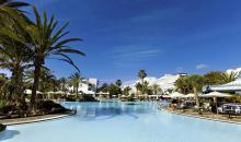 Blick auf den pool mit Liegebereich und Sonnenschirmen