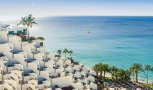 Blick über Hotelanlage auf Palmen und Meer