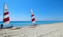 Strand mit kleinen weiß-roten Segelbooten