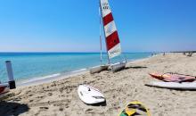 Strand mit Surfboards und kleinen Segelbooten