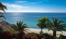 Blick über den Hotelgarten auf den Strand und das Meer