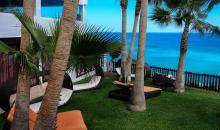 Blick vom Hotelgarten mit Liegemöglichkeiten auf das Meer
