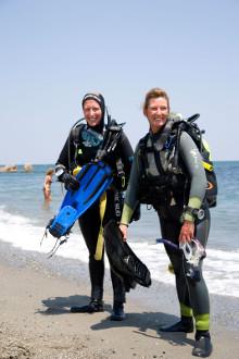 Zwei Taucherinnen stehen am Strand