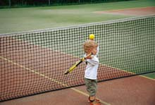 Kind vor dem Tennis-Netz