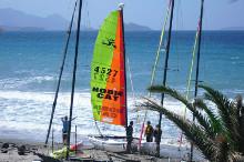 Katamaran mit Seglern am Strand